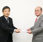成山理事長から受領証を受け取り高島さん(右)